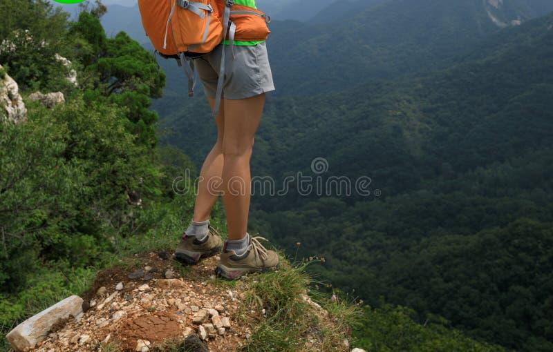 Kvinnafotvandraren tycker om sikten på överkanten av berget arkivfoto
