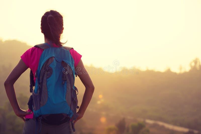 Kvinnafotvandraren tycker om sikten på soluppgång royaltyfri fotografi