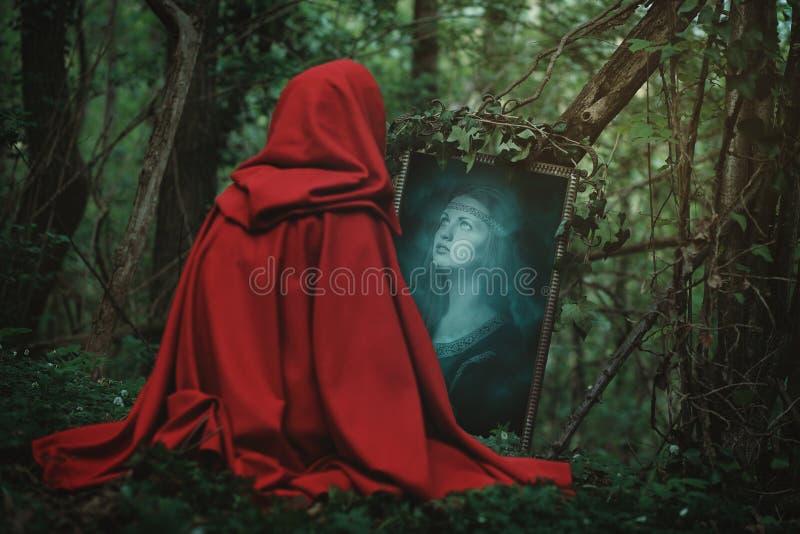 Kvinnaframsida i en magisk spegel arkivfoton