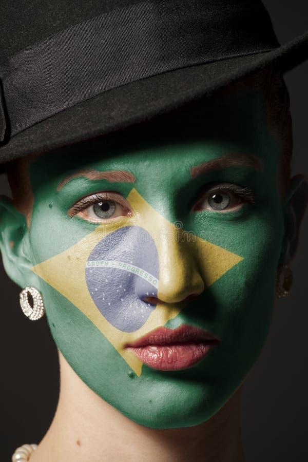 Kvinnaframsida med den målade flaggan av Brasilien arkivbilder