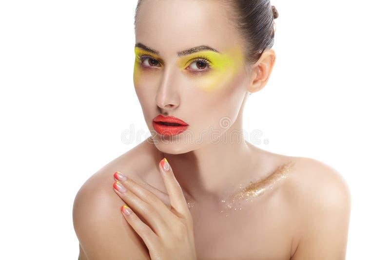 Kvinnaframsida med ljus gul makeup och manikyr arkivbilder