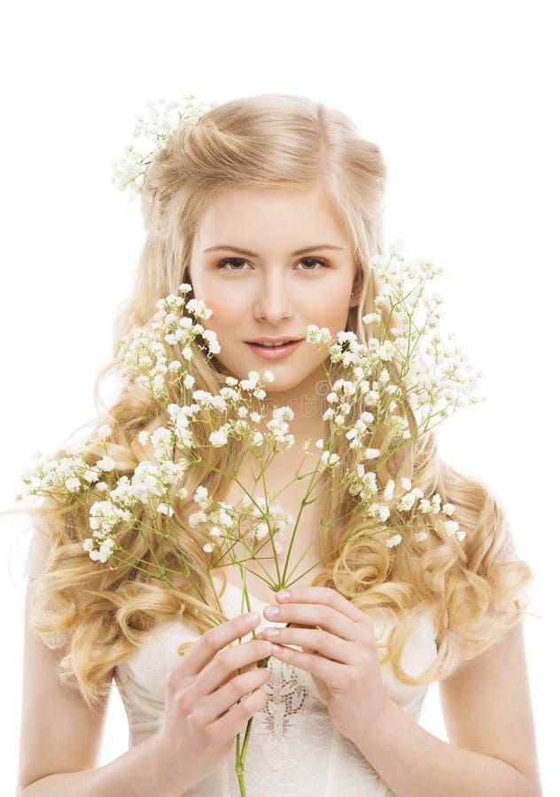 Kvinnaframsida och blommor över vit, flickamakeupstående royaltyfria foton