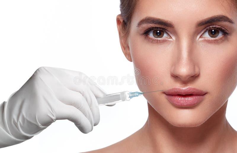 Kvinnaframsida och hand i handske med injektionssprutadanandeinjektionen royaltyfria foton