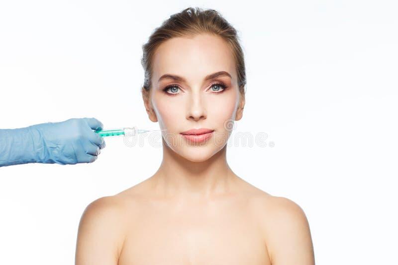 Kvinnaframsida och hand med injektionssprutadanandeinjektionen arkivbilder