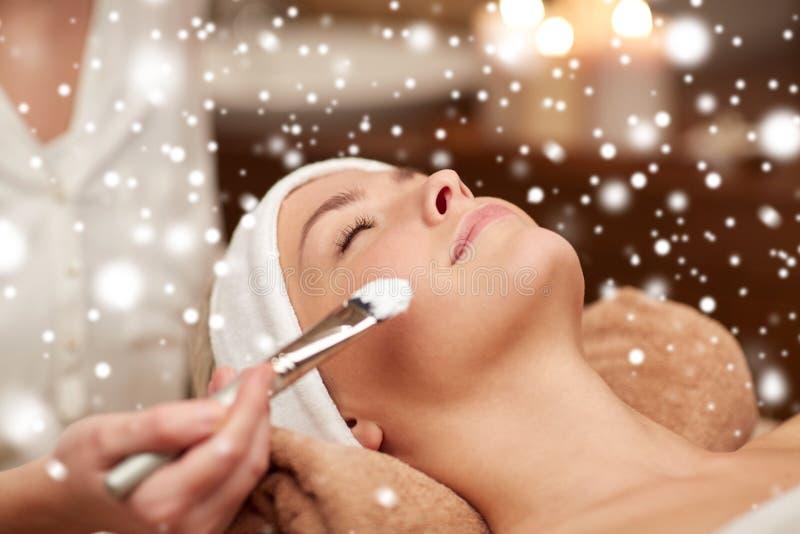 Kvinnaframsida och kosmetolog som applicerar maskeringen i brunnsort royaltyfri bild