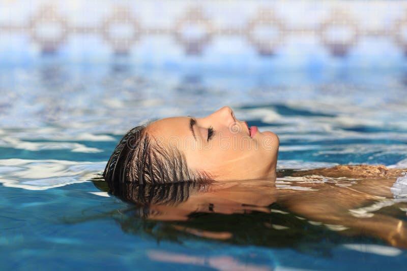 Kvinnaframsida som kopplar av att sväva på vatten av en pöl eller en brunnsort royaltyfri fotografi