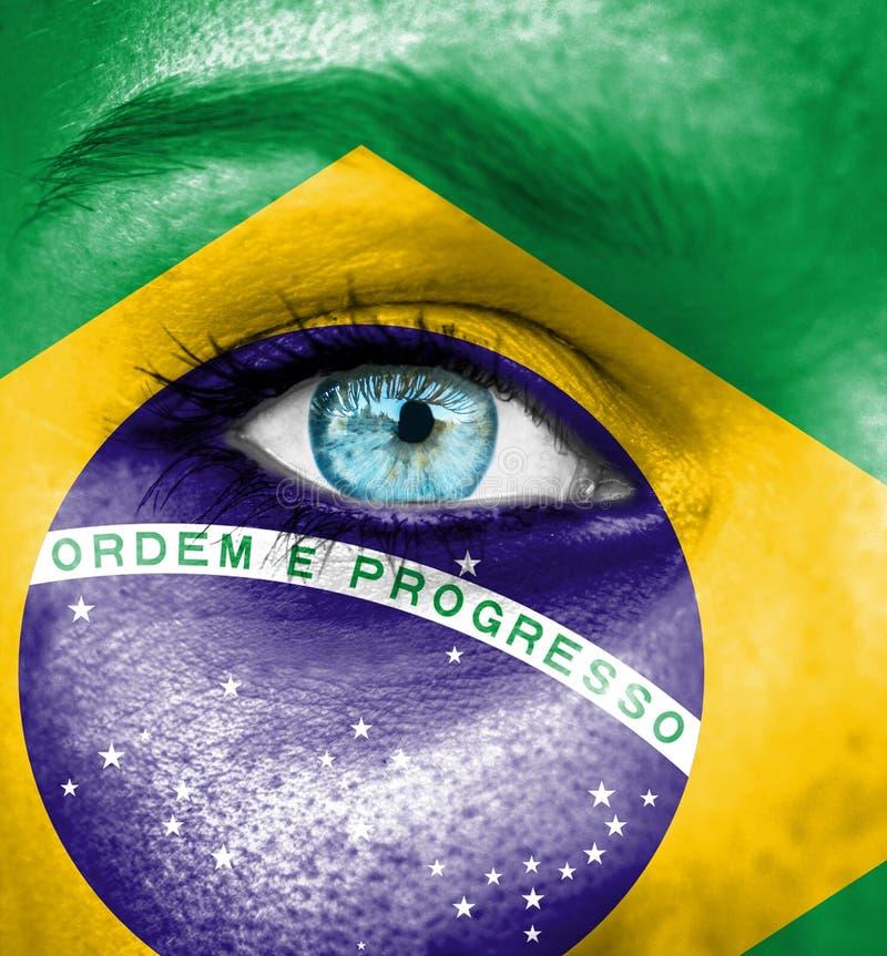 Kvinnaframsida som målas med flaggan av Brasilien royaltyfri fotografi