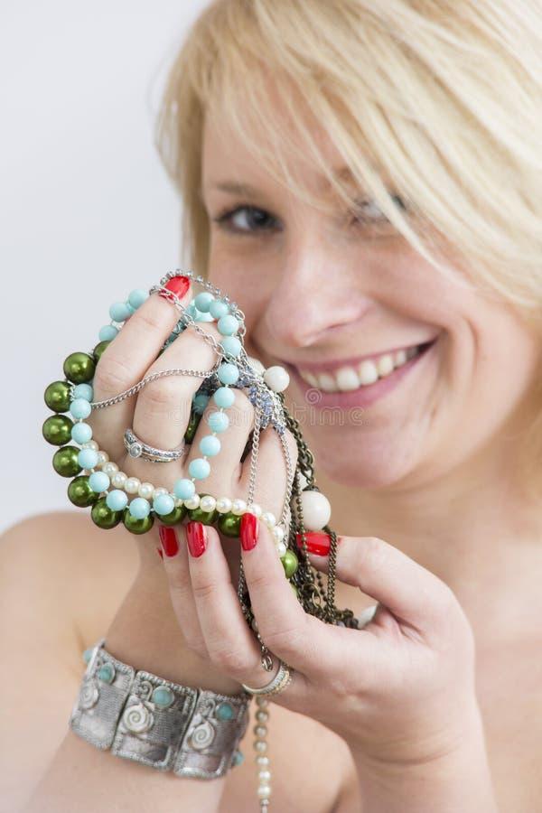 Kvinnaframsidan och händer med rött spikar och smycken arkivfoton
