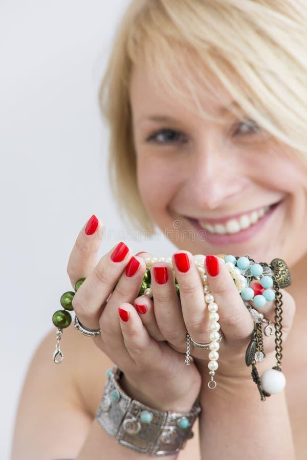 Kvinnaframsidan och händer med rött spikar och smycken arkivbilder