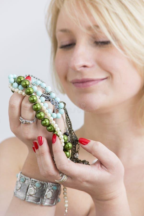Kvinnaframsidan och händer med rött spikar och smycken arkivbild