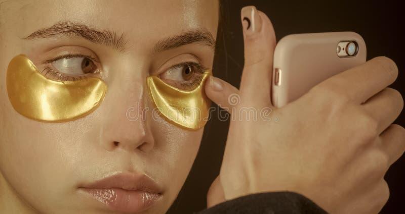 Kvinnaframsidaskönhet Skincare brunnsort, collagenmaskering under guld- färg för ögon från skrynklor royaltyfri bild