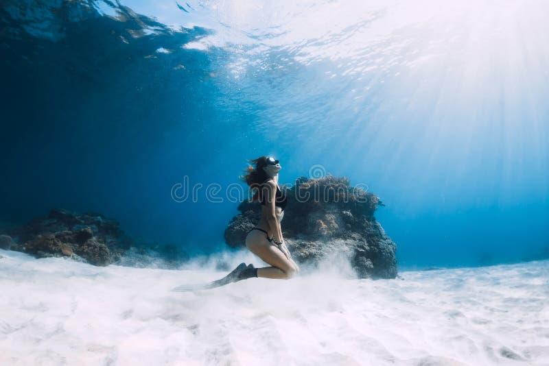 Kvinnafreediver med fena över det sandiga havet Undervattens- Freediving arkivbild