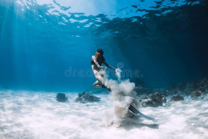 Kvinnafreediver med vita sandglidljud över det sandiga havet med fena Undervattens- Freediving arkivfoton