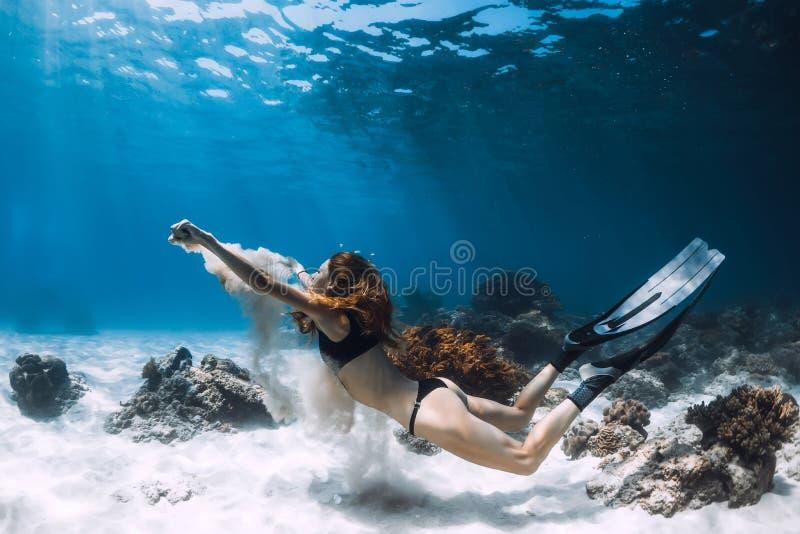 Kvinnafreediverbad som är undervattens- över sandig botten med sand arkivbild