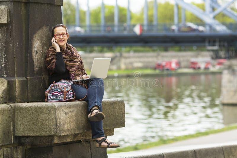 Kvinnafreelancersammanträde på steninvallningen av floden med en bärbar dator och samtal på telefonen royaltyfria foton