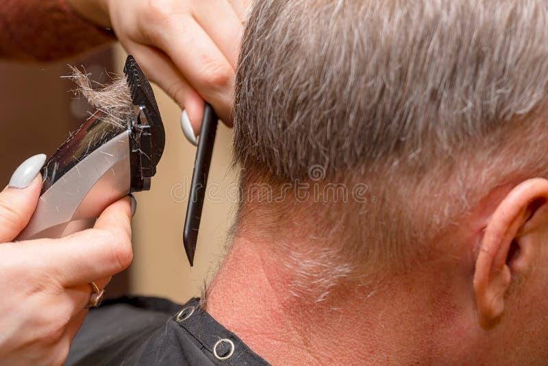 Kvinnafrisören klipper mannens hår med beskäraren för den elektriska clipperen arkivfoton