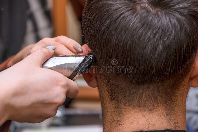 Kvinnafrisören klipper mannens hår med beskäraren för den elektriska clipperen arkivbilder
