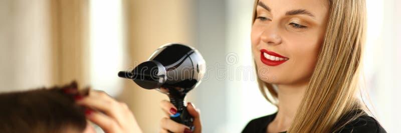 Kvinnafris?r Drying Male Hair med h?rtork royaltyfri foto