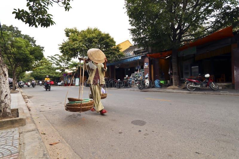 Kvinnagatuförsäljare som går i vägen i hoi ett Vietnam royaltyfri fotografi