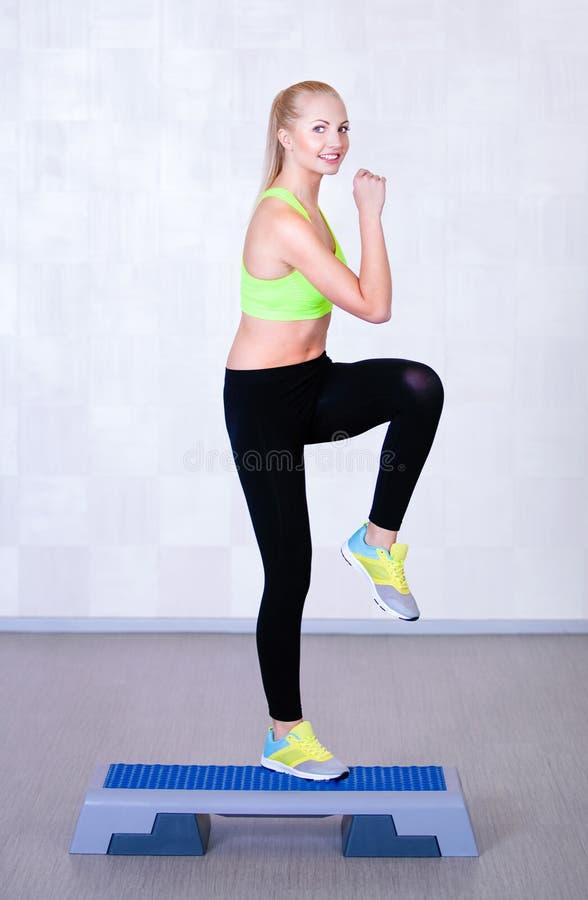 Kvinnagenomkörarekondition som gör aerobisk övning för moment arkivfoto