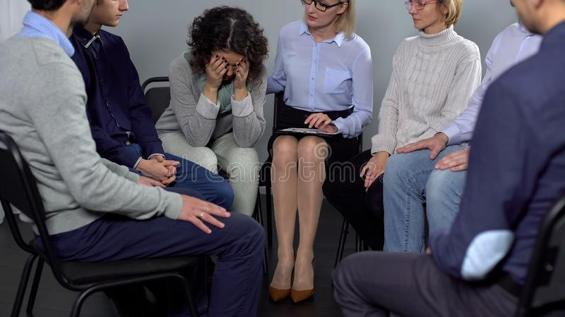 Kvinnagråt på terapiperioden, kvinnlig psykoterapeut som tröstar henne, hjälp royaltyfri foto