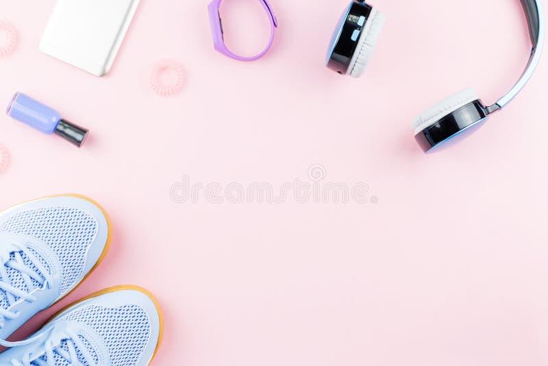 Kvinnagymnastikskor, hörlurar, konditionbogserare och smartphone på bakgrund för pastellfärgade rosa färger Sportmodebegrepp Lekm fotografering för bildbyråer