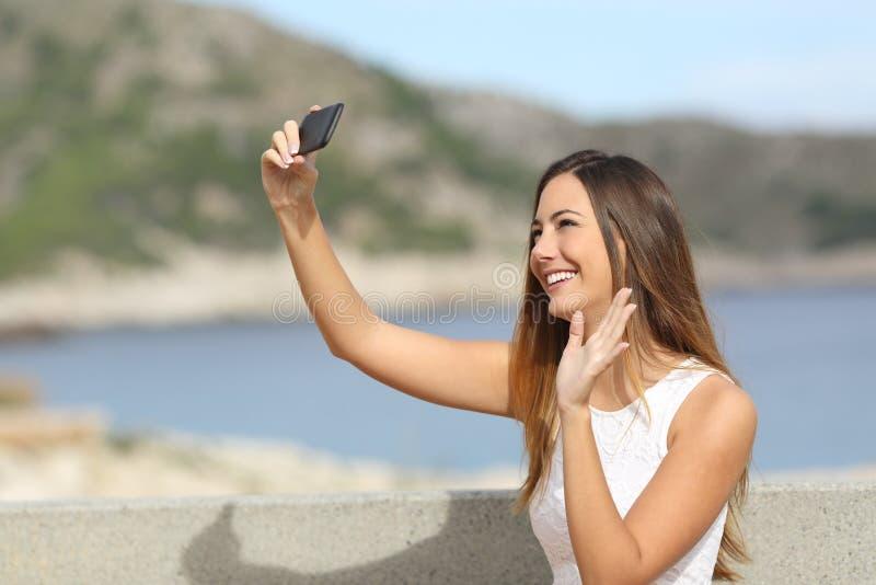 Kvinnahälsning, medan fotografera en selfie med en smartphone arkivbilder