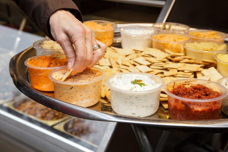 Kvinnahänder försöker laxen för majonnäs för köpet för chiper för sund för bunken för smakbrödsås mat för tomater den olika arkivbild
