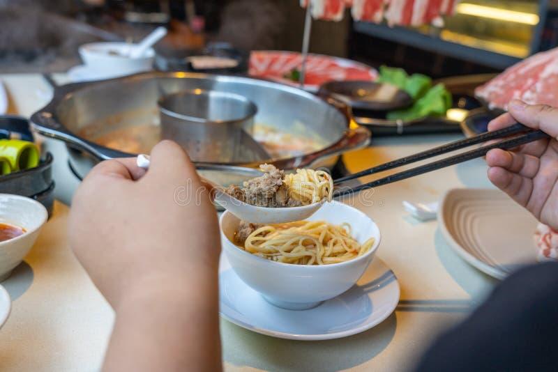Kvinnahänder genom att använda pinnar och skeden, medan äta hotpot royaltyfri foto