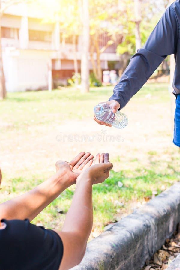 Kvinnahänder häller vatten från flaskan för rena händer Varmmast väder arkivbild