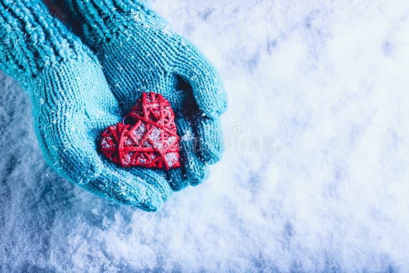 Kvinnahänder i den ljusa krickan stack tumvanten är hållande härlig flätad ihop röd hjärta för tappning i en snö St-valentinbegre royaltyfria bilder