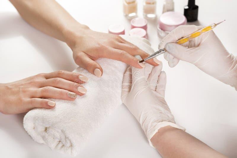Kvinnahänder i en manikyr för spikasalonghäleri med det yrkesmässiga hjälpmedlet fotografering för bildbyråer