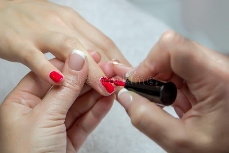 Kvinnahänder i en spikasalong som mottar en manikyr av en kosmetolog arkivbild