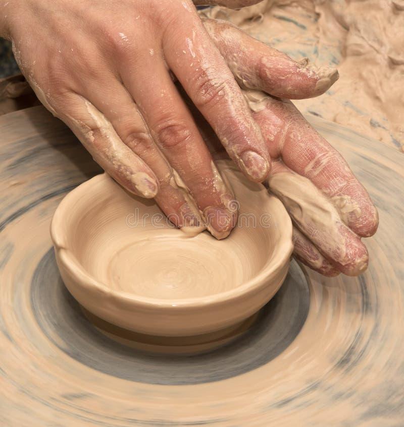 Kvinnahänder i lera på processen av danandelera bowlar på krukmakeriwh royaltyfria foton
