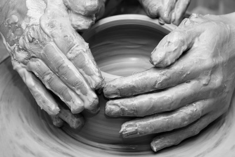 Kvinnahänder i lera på processen av danandelerkärl på krukmakeriwh royaltyfri fotografi