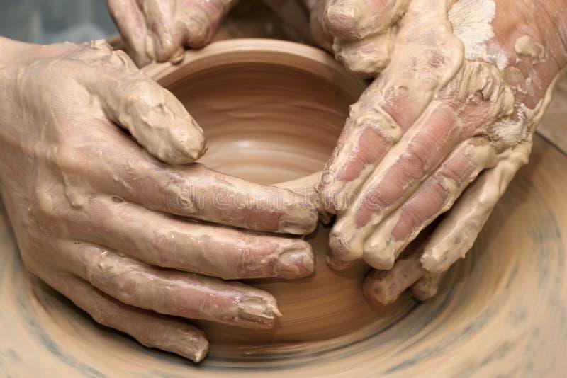 Kvinnahänder i lera på processen av danandelerkärl på krukmakeriwh arkivbild