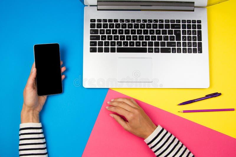 Kvinnahänder med den bärbar datordatoren och mobiltelefonen på färgrik bakgrund royaltyfria foton