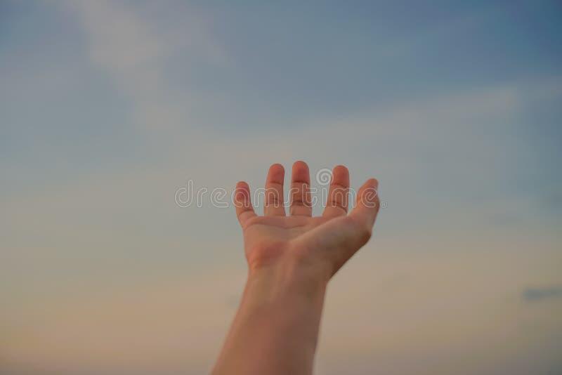 Kvinnahänder når ut till himlen som att be arkivfoton