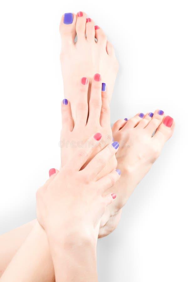 Kvinnahänder och ben med rött och blått spikar polermedel med urklippbanan arkivbilder