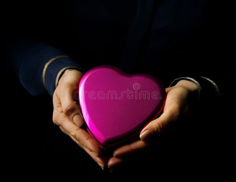 Kvinnahänder på den svart formade godisen för visningen hjärta boxas arkivfoto