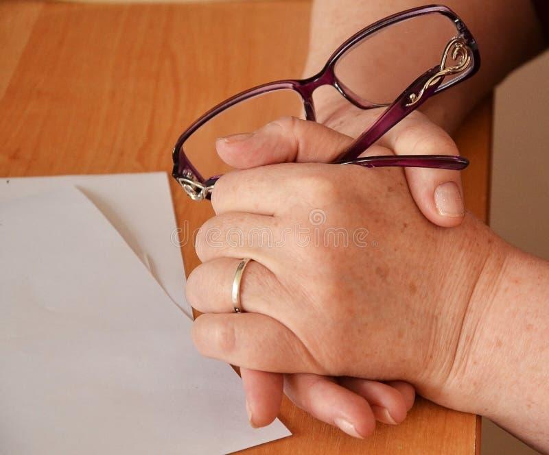 Kvinnahänder på tabellhållexponeringsglasen arkivfoto