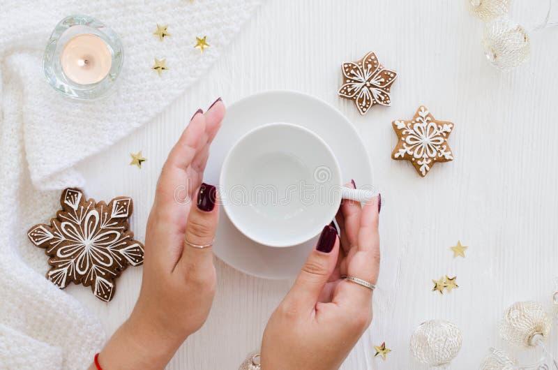 Kvinnahänder rymmer den tomma vita koppen Julpepparkaka fotografering för bildbyråer