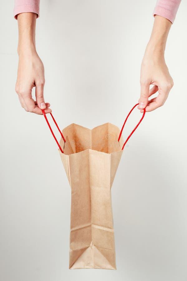 Kvinnahänder rymmer upp den öppna pappers- shoppingpåsen, slut fotografering för bildbyråer
