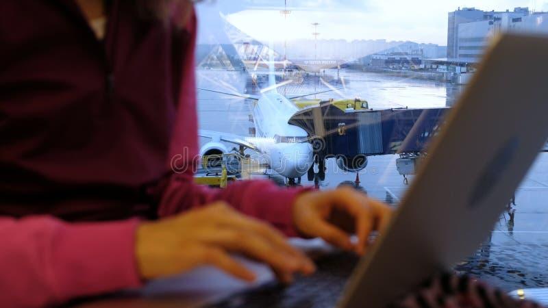 Kvinnahänder skriver på en bärbar dator vid fönstret på en flygplats på bakgrunden av en flygplannärbild arkivbilder