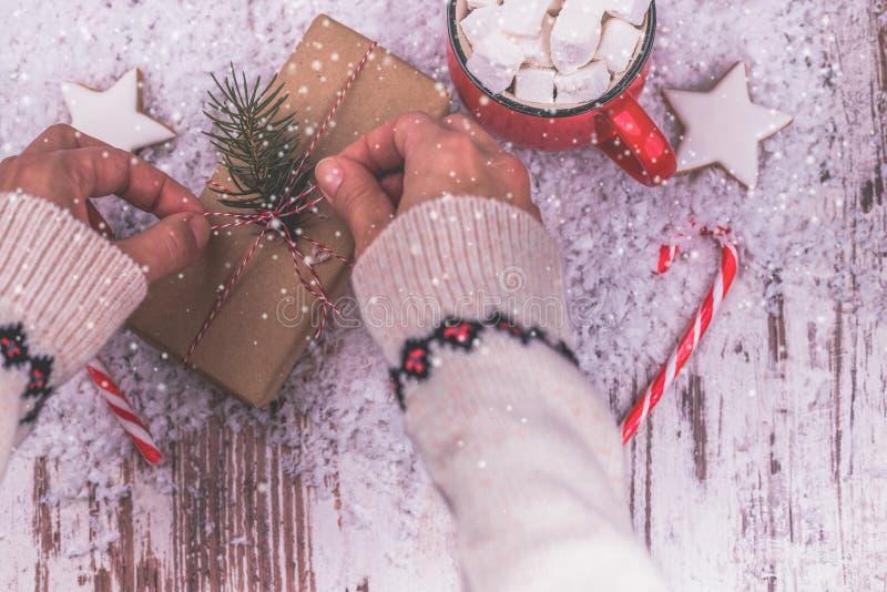 Kvinnahänder slår in jul semestrar handgjord gåva i hantverkpapper arkivbilder