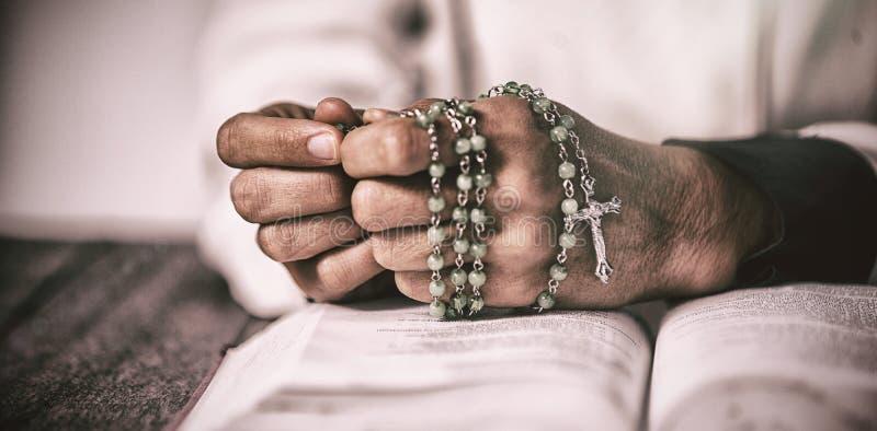 Kvinnahänder som ber med radbandet och bibeln royaltyfria bilder