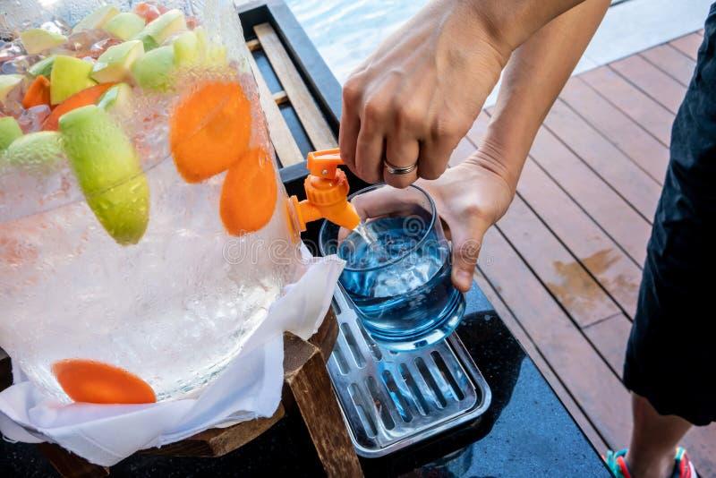 Kvinnahänder som drar ner spaken av vattenutmataren med frukt ingett vatten arkivfoton