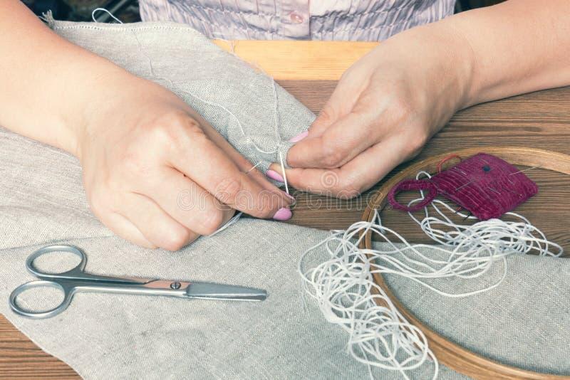 Kvinnahänder som gör openwork broderi arkivbilder