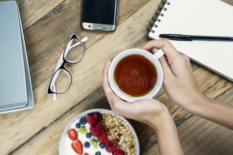 Kvinnahänder som rymmer en kopp te med yoghurt royaltyfri bild