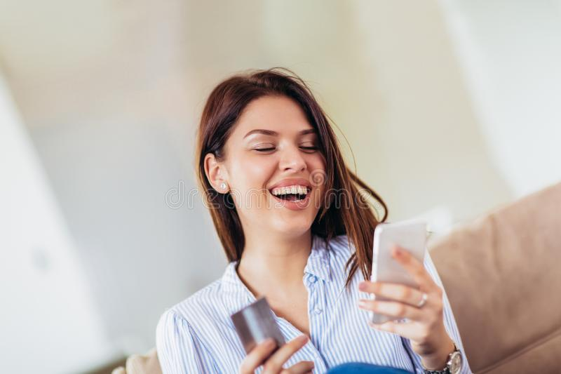Kvinnahänder som rymmer en kreditkort och använder den smarta telefonen för online-shopping arkivfoton
